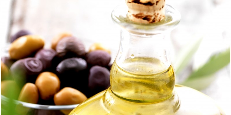 Bottle of olive oil and a bowl with black and green olives